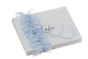 Cassie Blue Lace Wedding Garter with a Blue Bow and blue pearls on Garters and Co Gift Box