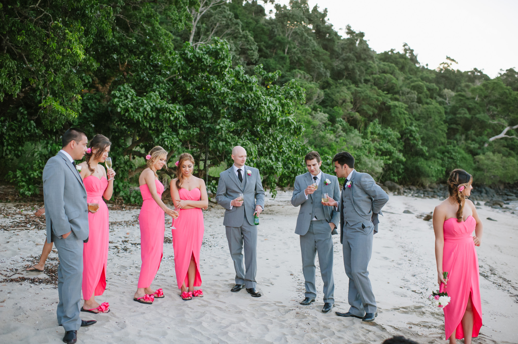 11a04b949d8a Bridesmaids wearing their hot pink bridal flip flops on the beach with  their partners