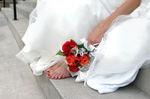 A Bride has taken off her uncomfortable shoes and is sitting down and resting her feet