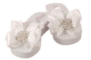 A pair of white Bridal Flip Flops with soft high wedge heels and embellished with pearls and rhinestones