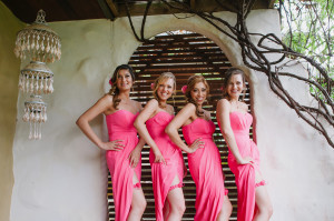 Four pretty Bridesmaids in hot pink dresses and matching garters