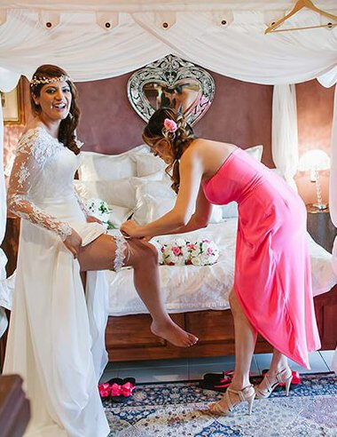Bridesmaid helping the Bride to slip her Wedding Garter onto her leg