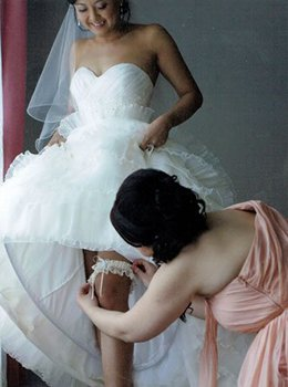 Bridesmaid helping Bride with Wedding Garters