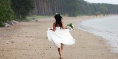 A Bride running down the Beach without any shoes on