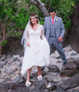 A Bride and Groom carefully walking over rocks to get to the Beach